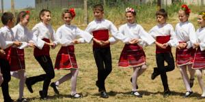 Bulgaarse kinderen in klederdracht dansen een traditionele rondedans