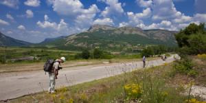 wandelaars langs een weg met in de achtergrond bergen